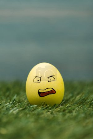Easter egg with aggressive facial expression on grass
