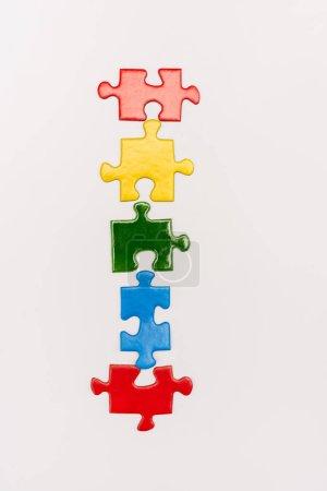 Foto de Vista superior de piezas brillantes y coloridas de rompecabezas aisladas sobre el concepto de autismo blanco. - Imagen libre de derechos