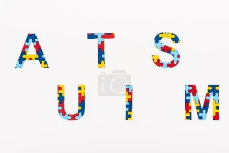 Photo pour Vue du dessus de l'inscription puzzle de l'autisme isolé sur blanc - image libre de droit