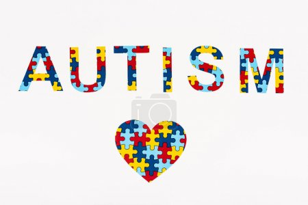Photo for Top view of puzzle heart and Autism lettering isolated on white - Royalty Free Image