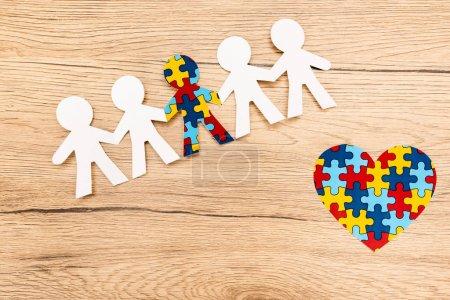 Photo pour Vue grand angle de l'enfant spécial avec autisme entre autres avec coeur décoratif sur fond en bois - image libre de droit