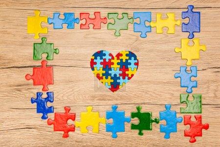 Photo pour Top view of decorative heart with pieces of puzzle on wooden background, autism concept - image libre de droit