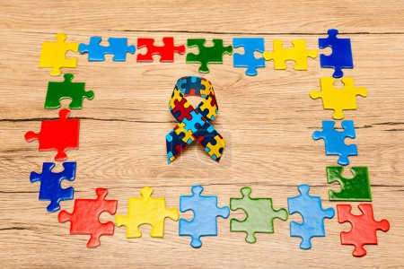 Photo pour High angle view of awareness ribbon with colorful pieces of puzzle on wooden background, autism concept - image libre de droit