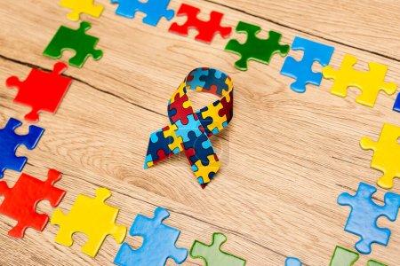 Photo pour Ruban de sensibilisation avec des pièces de puzzle sur fond en bois, concept d'autisme - image libre de droit