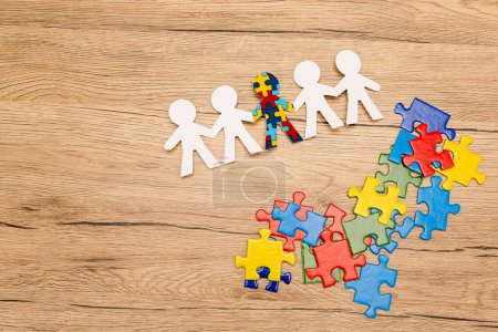 Photo for High angle view of special kid with autism among another and pieces of puzzle on wooden background - Royalty Free Image