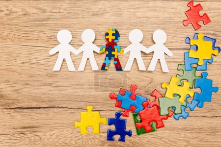 Photo pour Top view of special kid with autism among another and pieces of bright colorful puzzle on wooden background - image libre de droit