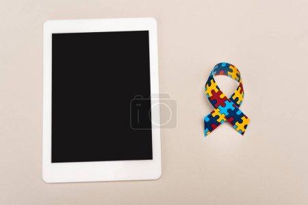 Photo pour Ruban de sensibilisation et tablette numérique sur fond blanc, concept d'autisme - image libre de droit