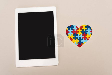 Photo for Top view of puzzle heart and digital tablet on white background, autism concept - Royalty Free Image