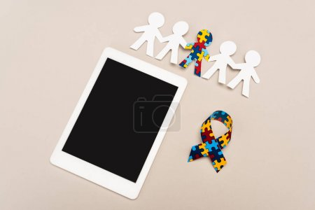 Photo pour High angle view of awareness ribbon, digital tablet and special kid with autism among another on white - image libre de droit