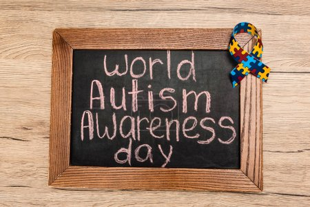Photo for Top view of board with world autism awareness day lettering and ribbon on wooden background - Royalty Free Image