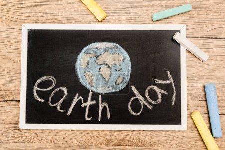 Photo pour Vue du dessus du tableau noir avec lettrage jour terre et morceaux de craie sur fond bois - image libre de droit