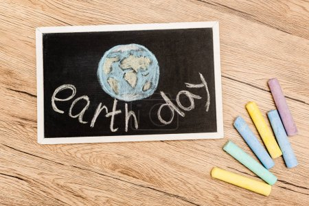 Photo pour Top view of board with earth day lettering and pieces of chalk on wooden background - image libre de droit