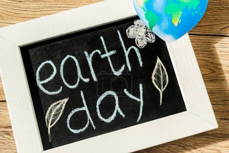 Photo pour Top view of black board with earth day lettering and globe on wooden background - image libre de droit