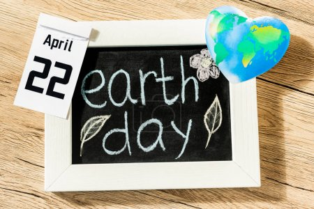 Photo pour Top view of board with earth day lettering, globe and calendar with 22 april inscription on wooden background - image libre de droit