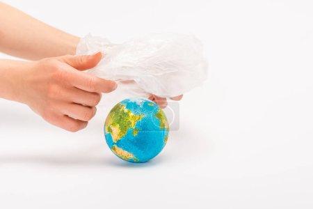 Photo pour Vue recadrée de la femme tenant un sac en plastique au-dessus du globe sur le concept de réchauffement climatique blanc - image libre de droit