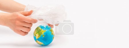Cropped view of woman holding plastic bag above globe on white, global warming concept