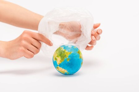 Photo pour Partial view of woman holding plastic bag above globe on white, global warming concept - image libre de droit