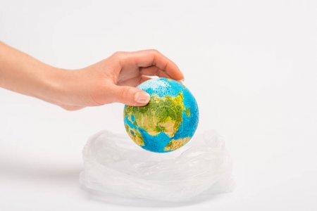 Cropped view of woman putting globe in plastic bag on white, global warming concept