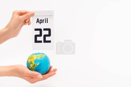 Photo pour Cropped view of woman holding calendar with 22 april inscription and globe on white background, earth day concept - image libre de droit