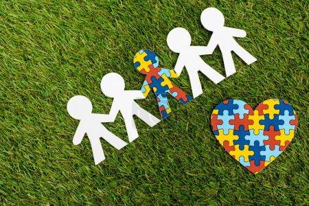 Photo pour Vue du dessus de l'enfant spécial avec autisme parmi un autre et coeur décoratif sur fond vert - image libre de droit