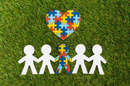 Photo for Top view of special kid with autism among another and decorative puzzle heart on green - Royalty Free Image