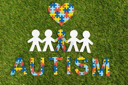 Photo pour Top view of autism puzzle lettering, decorative heart and special kid among another on green - image libre de droit
