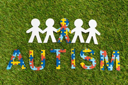 Photo pour Top view of autism puzzle lettering and special kid among another on green background - image libre de droit
