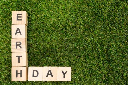 Foto de Top view of cubes with earth day lettering on green background - Imagen libre de derechos