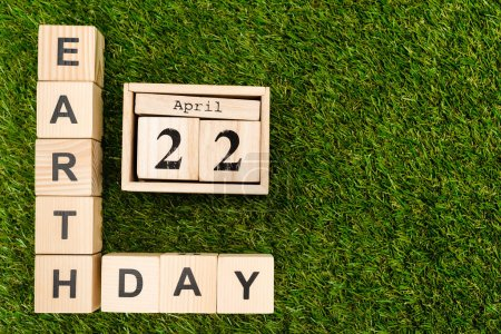 Photo pour Top view of cubes with earth day and 22 april lettering on green - image libre de droit