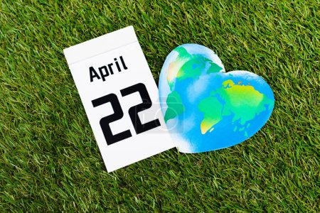 Photo pour Top view of calendar with 22 april inscription and globe on green background, earth day concept - image libre de droit