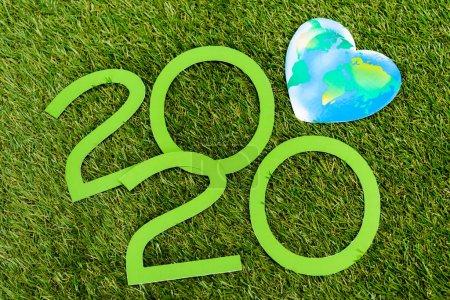 Foto de Vista superior de dígitos 2020 y globo sobre fondo verde, concepto del día de la tierra - Imagen libre de derechos