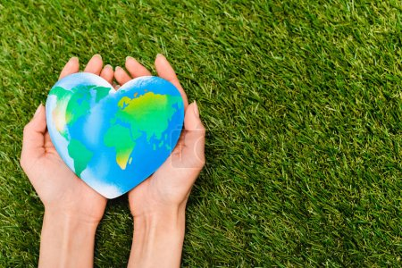Cropped view of globe in female hands on green, earth day concept