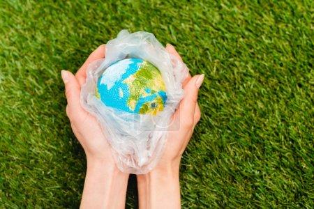 Photo pour Vue agrandie d'un sac en plastique avec globe dans les mains de la femme sur vert, concept de réchauffement global - image libre de droit