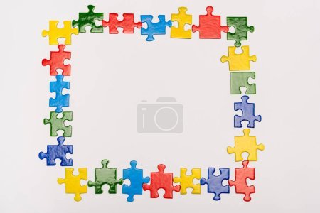 Photo for Top view of frame with bright pieces of puzzle isolated on white, autism concept - Royalty Free Image