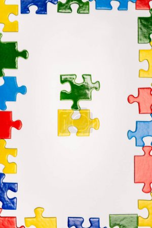 Photo for Top view of frame with bright multicolored pieces of puzzle isolated on white, autism concept - Royalty Free Image