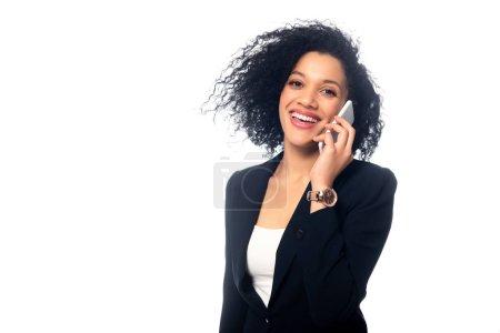 Photo pour Une femme d'affaires américaine d'origine africaine parle sur un téléphone intelligent, sourit et regarde une caméra isolée sur un blanc - image libre de droit