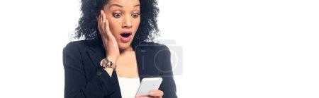 Photo pour Femme afro-américaine choquée avec la bouche ouverte regardant smartphone isolé sur blanc, plan panoramique - image libre de droit