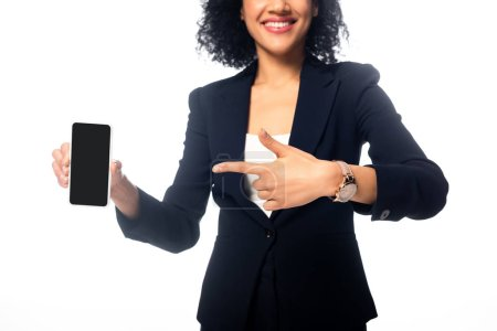 Photo for Cropped view of african american woman pointing at smartphone and smiling isolated on white - Royalty Free Image