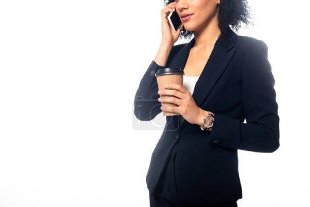 Photo pour Vue granuleuse d'une femme d'affaires américaine d'origine africaine parlant sur un téléphone intelligent et tenant une tasse de café jetable isolée sur du blanc - image libre de droit