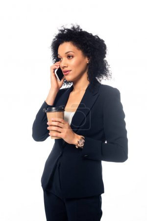 African american businesswoman talking on smartphone and holding disposable cup of coffee isolated on white