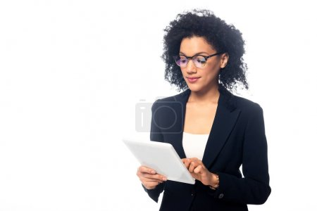 Photo for Successful african american businesswoman in glasses looking at digital tablet isolated on white - Royalty Free Image