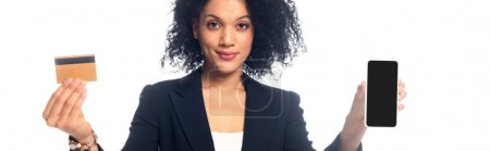 African american businesswoman presenting credit card and smartphone and smiling isolated on white, panoramic shot