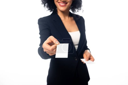 Cropped view of african american businesswoman smiling and presenting business card isolated on white
