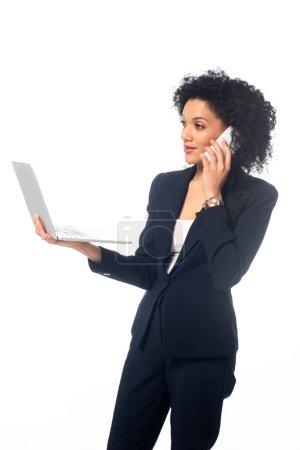 Photo pour Femme d'affaires afro-américaine réussie tenant un ordinateur portable et parlant au téléphone isolé sur blanc - image libre de droit