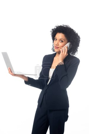 Photo for Successful african american businesswoman looking at camera, holding laptop and talking on phone isolated on white - Royalty Free Image