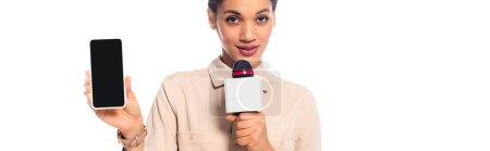 Photo pour Journaliste afro-américain parlant dans le microphone et présentant smartphone isolé sur blanc, panoramique - image libre de droit