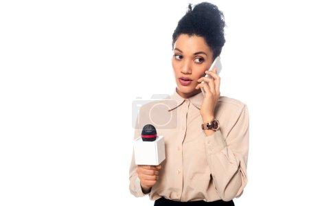 Photo pour Vue de face du journaliste afro-américain avec microphone parlant sur smartphone isolé sur blanc - image libre de droit