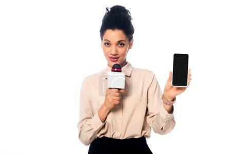 Photo pour Journaliste afro-américain parlant dans le microphone et présentant smartphone isolé sur blanc - image libre de droit