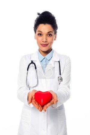 Photo pour Vue de face du docteur africain américain avec stéthoscope souriant et montrant le coeur décoratif isolé sur blanc - image libre de droit