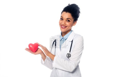Photo for African american doctor with stethoscope smiling and showing decorative red heart isolated on white - Royalty Free Image